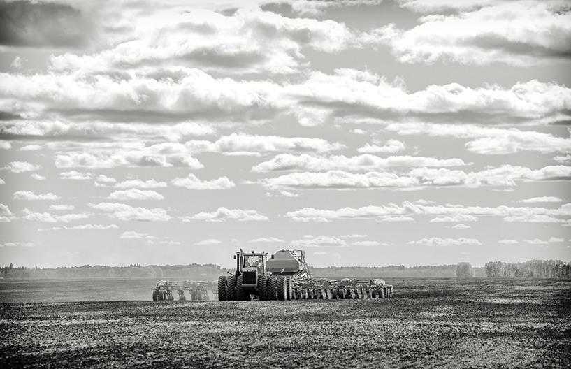 A tractor pulling a seeder and fertilizer tanks planting a crop in a black and white countryside summer landscape